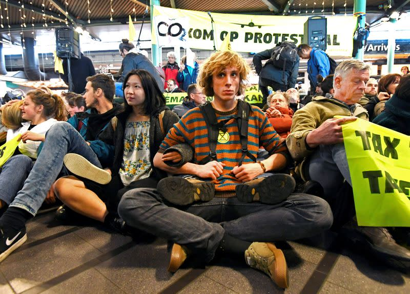 People demonstrate as Greenpeace stages a climate protest at Amsterdam Schiphol Airport in Schiphol