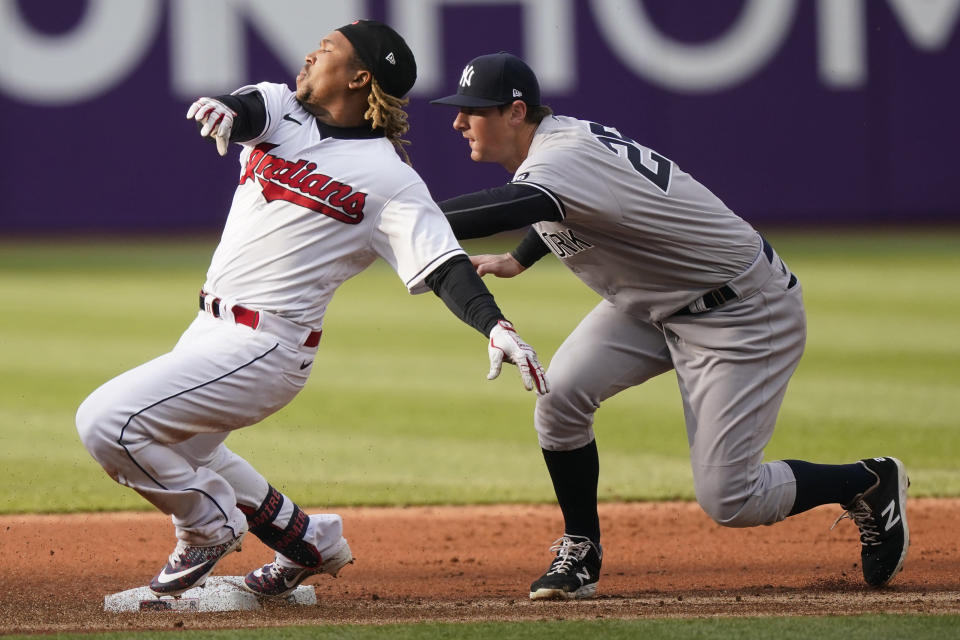 Cleveland Indians' Jose Ramirez, left, is safe at second base with a double as New York Yankees' DJ LeMahieu is late on the tag in the first inning of a baseball game, Thursday, April 22, 2021, in Cleveland. (AP Photo/Tony Dejak)