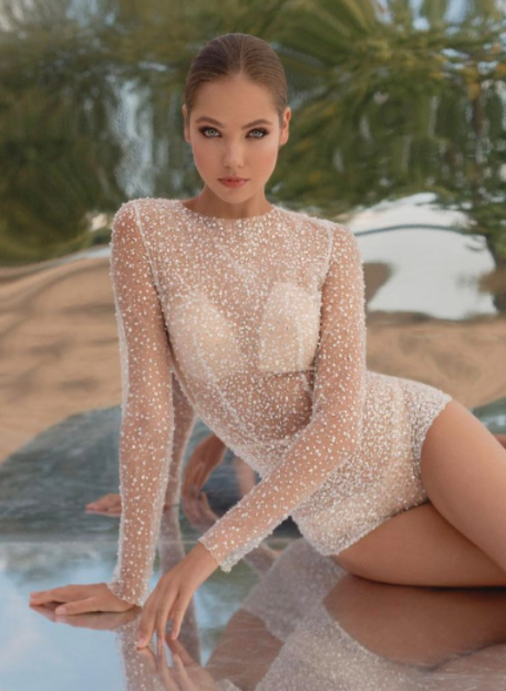 Model wears bodysuit version of wedding dress with bra cup and underwear visible