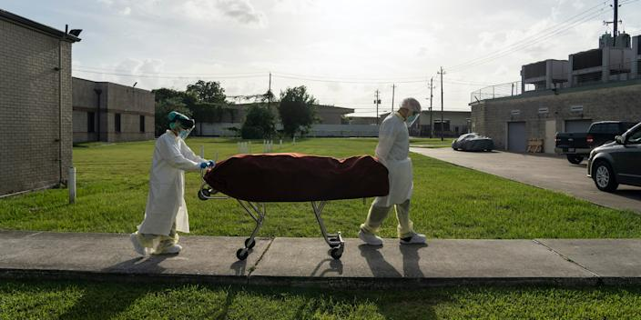 Medical staff wearing full PPE push a stretcher with a deceased patient to a car outside of the COVID-19 intensive care unit at the United Memorial Medical Center on June 30, 2020 in Houston, Texas.