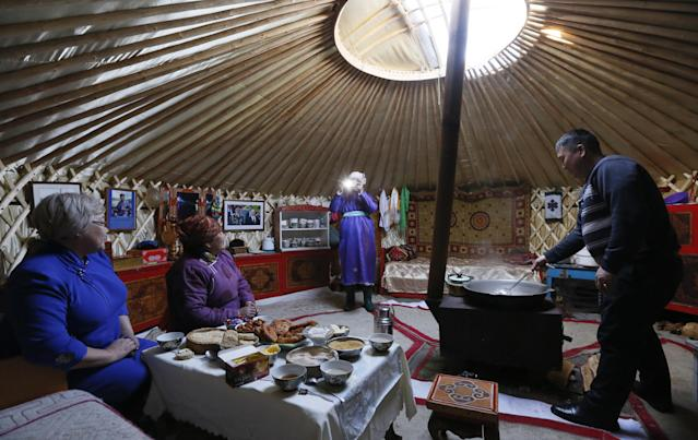 <p>Tanzurun Darisyu, second from left, head of a Tuvan private farm in the Kara-Charyaa area, has a meal with her neighbours and relatives inside a yurt south of Kyzyl town, the administrative center of the Republic of Tuva (Tyva region) in southern Siberia, Russia, on Feb. 14, 2018. (Photo: Ilya Naymushin/Reuters) </p>