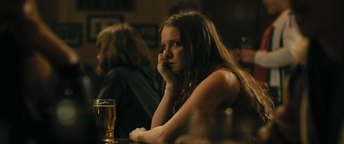 A woman leans her chin on her hand as she sits in a bar with a glass of beer.