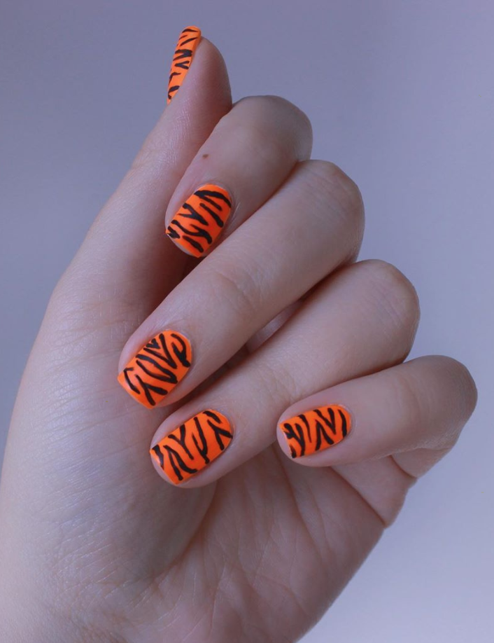 """<p>Going with a feline-theme this year? Try this bright orange tiger-striped look to match your nails to your costume. Juli, the nail artist who created this look, has a <a href=""""https://www.instagram.com/p/B1cUpSPH2CY/"""" rel=""""nofollow noopener"""" target=""""_blank"""" data-ylk=""""slk:quick video tutorial"""" class=""""link rapid-noclick-resp"""">quick video tutorial</a> to help you expertly swipe on those tiger stripes.</p><p><a class=""""link rapid-noclick-resp"""" href=""""https://www.amazon.com/China-Glaze-Lacquer-Orange-Knockout/dp/B00185PF06?tag=syn-yahoo-20&ascsubtag=%5Bartid%7C10072.g.33239588%5Bsrc%7Cyahoo-us"""" rel=""""nofollow noopener"""" target=""""_blank"""" data-ylk=""""slk:SHOP POLISH"""">SHOP POLISH</a></p>"""