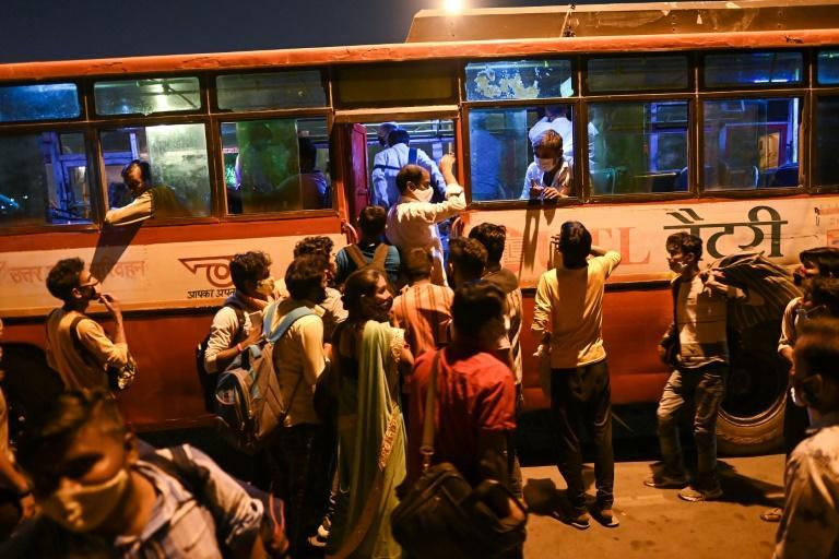 People scramble to board a bus in New Delhi to head to their hometowns as a week-long lockdown comes into effect in the Indian capital due to a spike in coronavirus cases