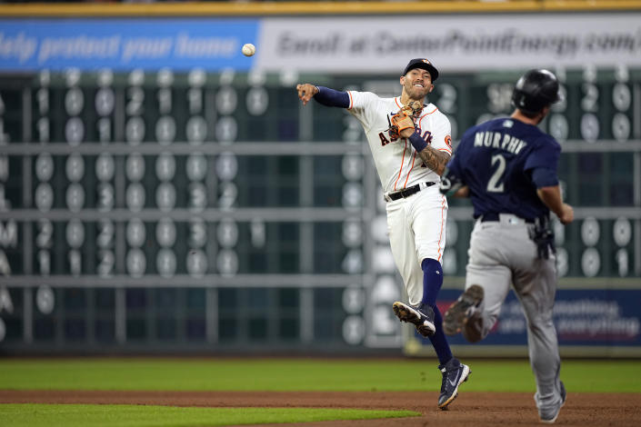 Houston Astros shortstop Carlos Correa, left, throws to first for a double play as Seattle Mariners' Tom Murphy (2) runs toward second base during the seventh inning of a baseball game Tuesday, Sept. 7, 2021, in Houston. Murphy was out at second and Jake Bauers was out at first on the double play. (AP Photo/David J. Phillip)