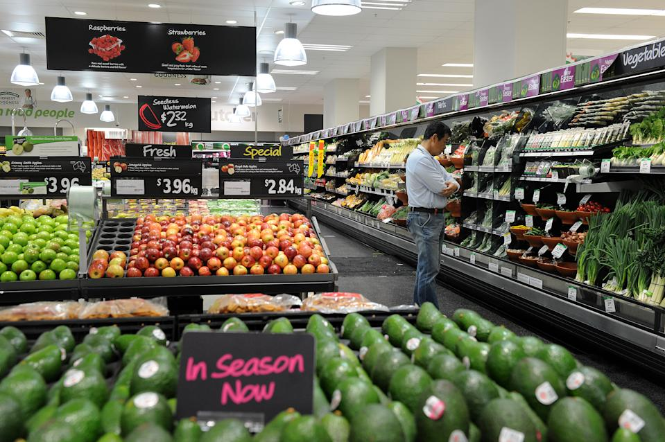 A shopper looks at produce in the fruit and vegetable section inside a Woolworths grocery store in Brisbane.