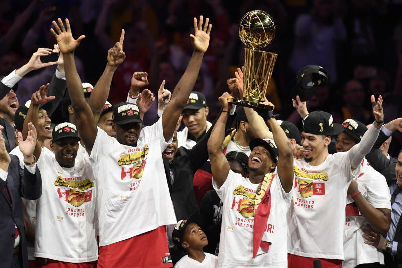 Toronto Raptors guard Kyle Lowry, center right, holds Larry O'Brien NBA Championship Trophy after the Raptors defeated the Golden State Warriors 114-110 in Game 6 of basketball's NBA Finals, Thursday, June 13, 2019, in Oakland, Calif. (Frank Gunn/The Canadian Press via AP)