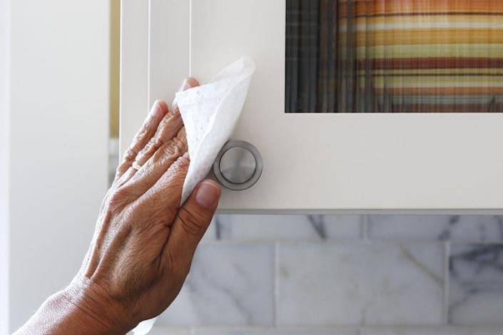 """<p>According to The Spruce, most cabinet types — including metal, plastic laminate, painted wood, and vinyl cabinets — can be cleaned with a solution of liquid dish soap and warm water. Use a spray bottle full of that solution and a cloth to <a href=""""https://www.thespruce.com/steps-to-clean-kitchen-cabinets-1900630"""" rel=""""nofollow noopener"""" target=""""_blank"""" data-ylk=""""slk:wipe down the exterior of your cabinets"""" class=""""link rapid-noclick-resp"""">wipe down the exterior of your cabinets</a>, and then thoroughly dry. For tough stains, try using a paste of baking soda and water and a soft-bristled brush. </p><p>Once the exteriors are clean, empty each cabinet and vacuum out any residue or crumbs. Then you can wash the interior of the cabinets with warm water and a mild detergent and thoroughly dry. It's a good idea to wipe down dusty cans and containers with warm water and dish soap as well. </p>"""