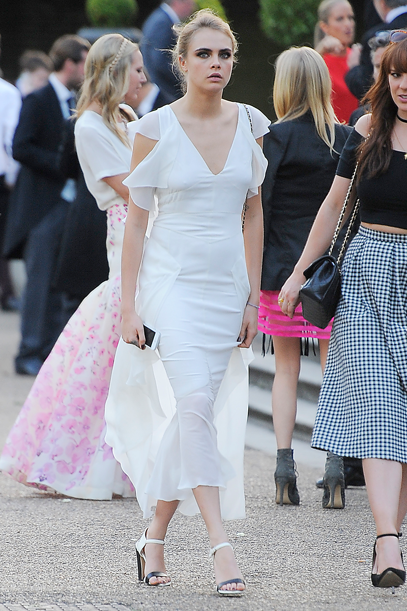 <p>Cara Delevinge was a bridesmaid for sister Poppy Delevingne's wedding, for which she wore this V-neck white dress with flutter sleeve details.</p>