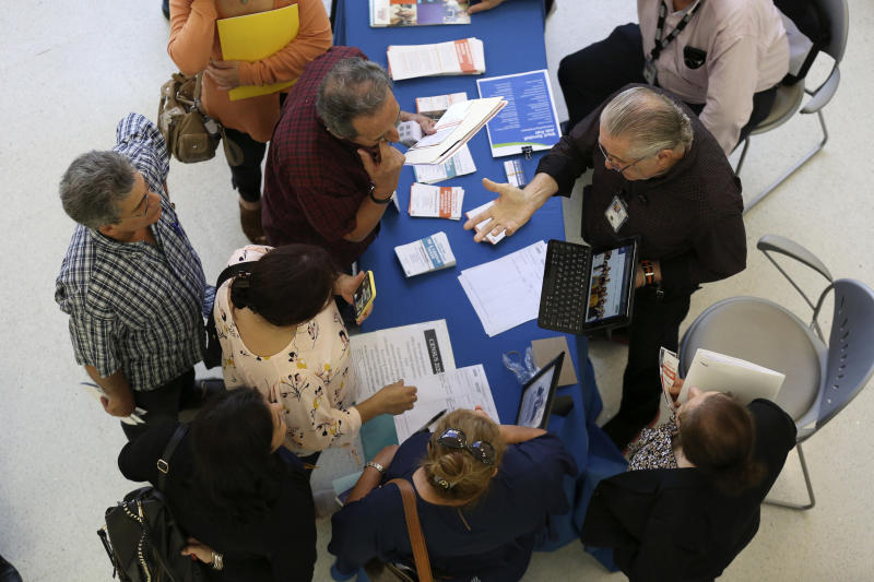 FILE - In this Sept. 18, 2019 file photo, Alex Pereira, of the U.S. Census Bureau, right, talks with job applicants about temporary positions available with the 2020 Census, during a job fair designed for people fifty years or older, in Miami. The U.S. Census Bureau said it has reached its goal of recruiting more than 2.6 million applicants for the once-a-decade head count that launched for most of America this week — but it has been a bumpy road getting there.   (AP Photo/Lynne Sladky, File)
