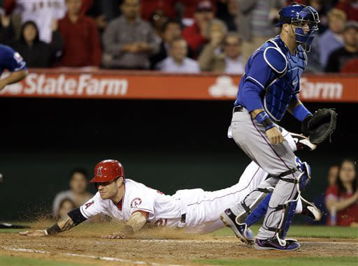 Los Angeles Angels' Josh Hamilton, bottom, scores on a double by Howie Kendrick as Texas Rangers catcher A.J. Pierzynski, right, waits for a throw during the fourth inning of a baseball game in Anaheim, Calif., Monday, April 22, 2013. (AP Photo/Jae C. Hong)