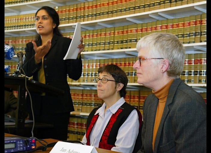 FILE - Jayashri Srikantiah, staff attorney with the ACLU of Northern California, holds up copies of records showing passengers checked on no fly lists from San Francisco International Airport, as plaintiffs Jan Adams, right, and Rebecca Gordon, center, look on during a news conference in San Francisco, in this April 22, 2003 file photo. The American Civil Liberties Union has sued the government on behalf of Americans who believe they're on the no-fly list and have not been able to travel by air for work or to see family. The no-fly list has swelled to 20,000 people before, such as in 2004. At the time, people like the late Sen. Ted Kennedy were getting stopped before flying _ causing constant angst and aggravation for innocent travelers. But much has changed since then. (AP Photo/Eric Risberg, File)