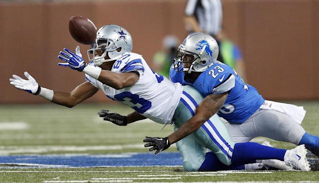 Dallas Cowboys wide receiver Terrance Williams (83) reaches for a pass as Detroit Lions cornerback Chris Houston (23) defends in the second half of an NFL football game in Detroit, Sunday, Oct. 27, 2013. (AP Photo/Rick Osentoski)