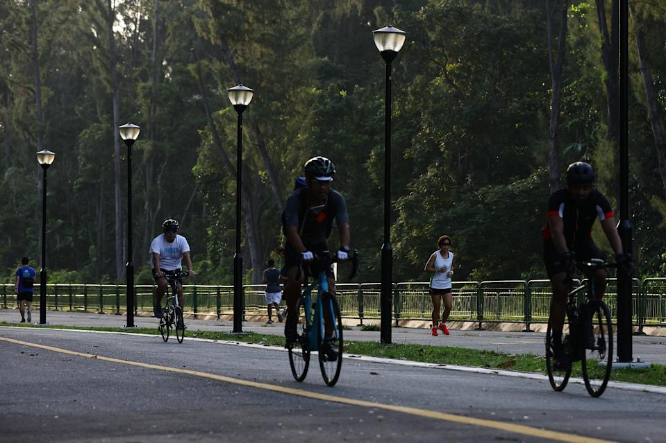 SINGAPORE - APRIL 10:  People are seen jogging and cycling at a park on April 10, 2020 in Singapore. The Singapore government announced it will close open-air stadiums after people continued to disregard social-distancing rules by exercising in groups. The authority warned it will further tighten access to parks for non-compliance and urged park goers not to exercise, jog or cycle in groups to help prevent more coronavirus (COVID-19) clusters from emerging in the community.  (Photo by Suhaimi Abdullah/Getty Images)
