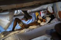 Hady Baye, 31, rests in a bunk bed at the Modern Christian Mission Church in Fuerteventura, one of the Canary Islands, Spain, on Saturday, Aug. 22, 2020. The Modern Christian Mission is the main shelter for rescued migrants on the island of Fuerteventura. Some 4,000 migrants have reached the Canaries so far this year, the most in over a decade, raising alarm at the highest levels of the Spanish government. (AP Photo/Emilio Morenatti)