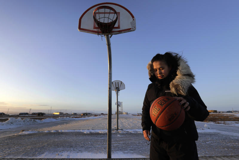 In this Feb. 17, 2019, photo, Deidre Levi carries her basketball as she walks to work in the Native Village of St. Michael, Alaska. Levi says she spoke up about being sexually assaulted because she wanted to be a role model for girls in Alaska. (AP Photo/Wong Maye-E)