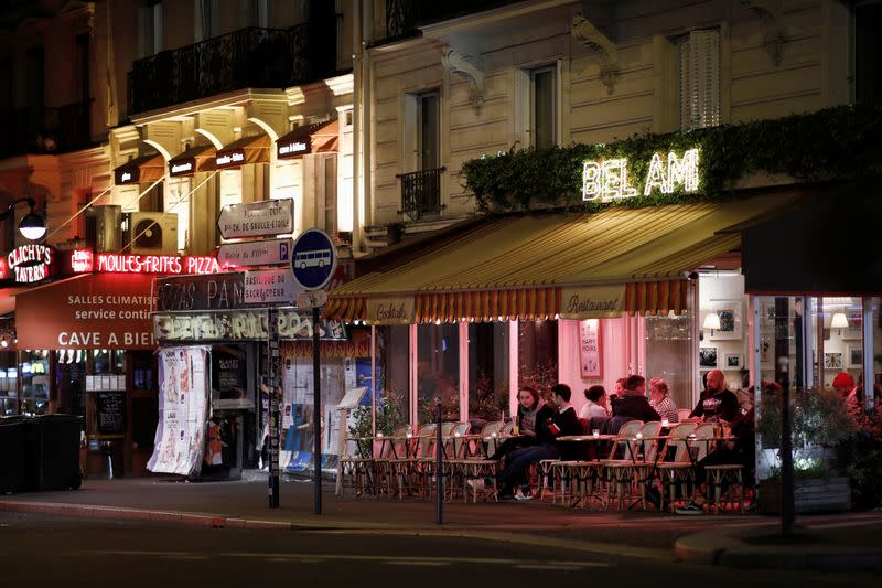 FILE PHOTO: People enjoy a drink outside a bar in Paris