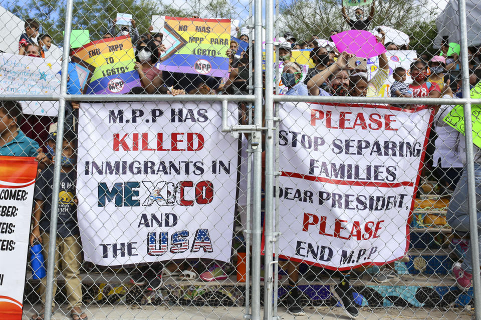 """FILE - In this Oct. 25, 2020, file photo, people press signs against a closed gate to the migrant encampment, asking then President Donald Trump to end the Migrant Protection Protocols during a rally at the encampment in Matamoros, Tamaulipas, Mexico. The Supreme Court has ordered the reinstatement of the """"Remain in Mexico"""" policy, saying that the Biden administration likely violated federal law by trying to end the Trump-era program that forces people to wait in Mexico while seeking asylum in the U.S. (Denise Cathey/The Brownsville Herald via AP, File)"""