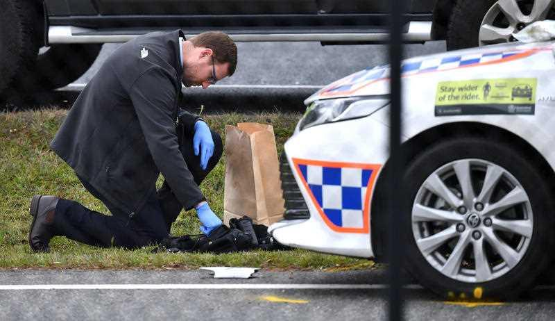 A Queensland Police officer is seen investigating the scene where 53-year-old Senior Constable David Masters was killed on the Bruce Highway at Burpengary in Brisbane.