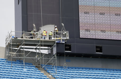 Workers install a Carolina Panthers logo as one of the ledge video boards is tested at the team's home football field, Bank of America Stadium, in Charlotte, N.C., Wednesday, June 25, 2014. (AP Photo/Chuck Burton)
