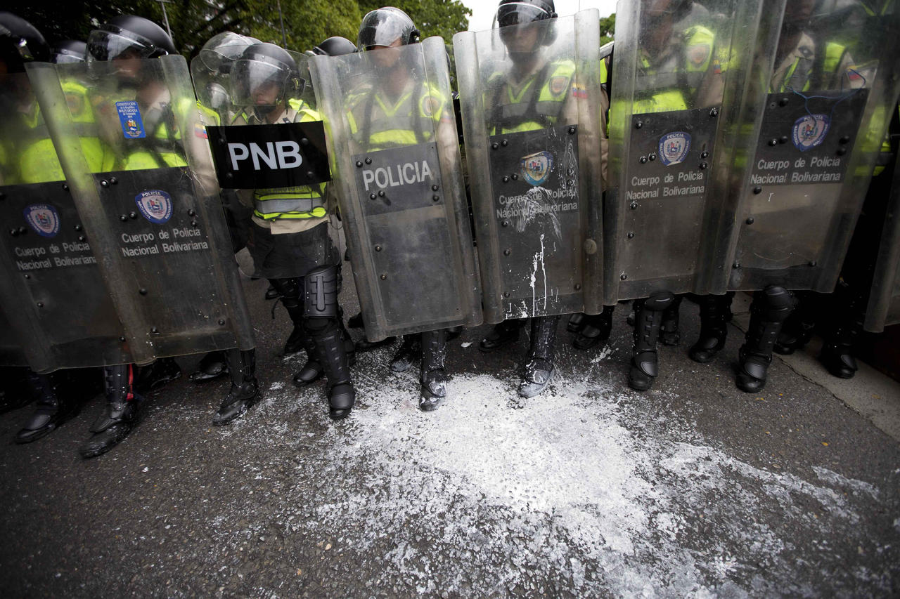 <p>White paint thrown by protesters covers the boots of Bolivarian National Police, who block an opposition march in Caracas, June 7, 2016. (AP/Ariana Cubillos) </p>