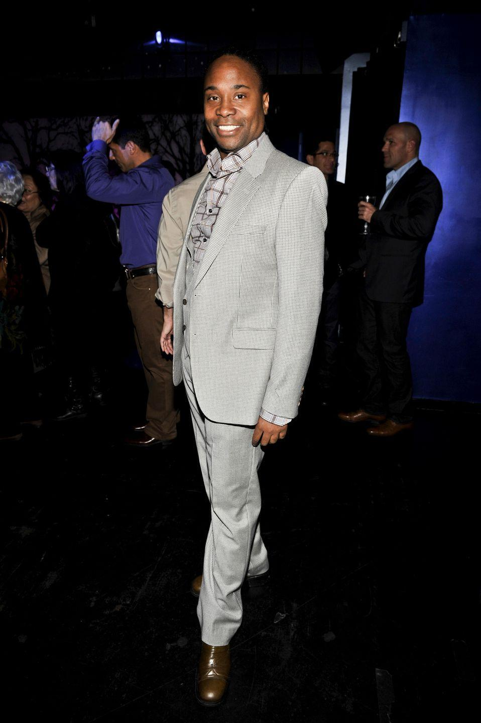 <p>Porter poses at the Broadway Takes the Runway event in a checkered button-down, a gray suit, and brown boots. </p>