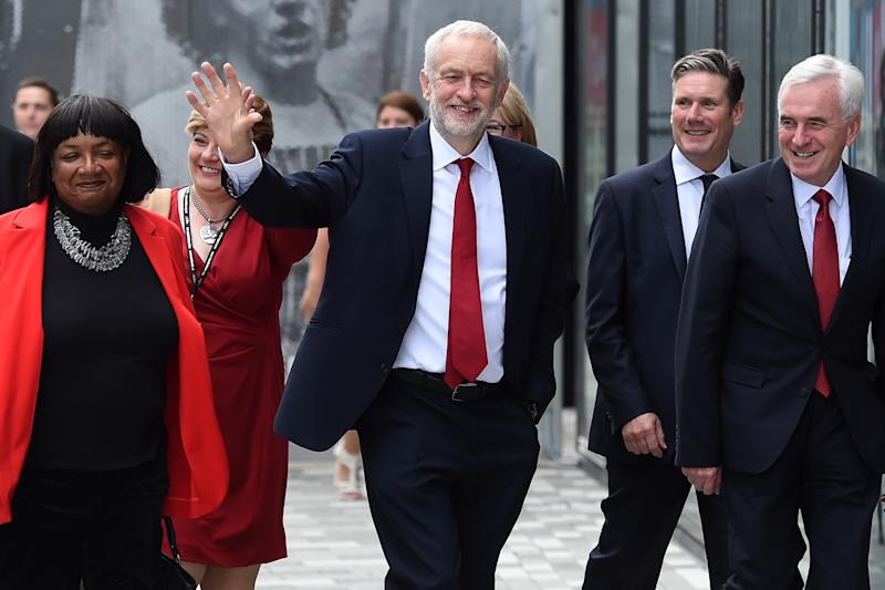 Britain's opposition Labour Party leader Jeremy Corbyn (C) arrives with shadow home secretary Diane Abbott (L) and shadow chancellor John McDonnell (R) at the convention hall to address delegates on the final day of the Labour party conference in Liverpool, north west England on September 26, 2018. (Photo by Paul ELLIS / AFP) (Photo credit should read PAUL ELLIS/AFP/Getty Images)
