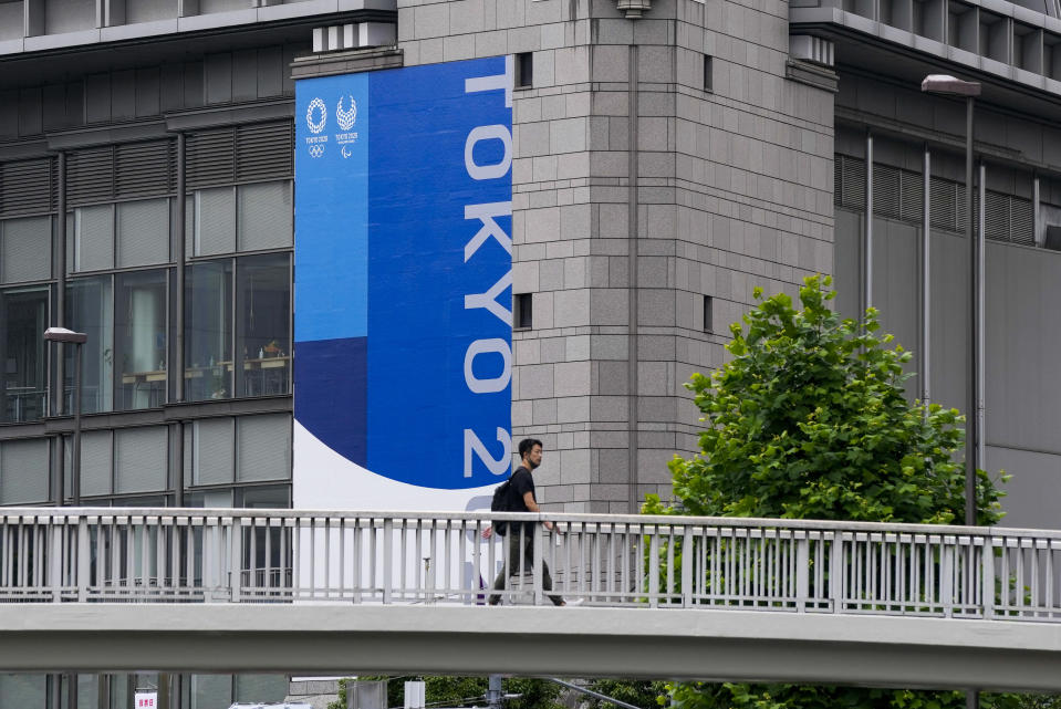 A person wearing a protective mask walks over a pedestrian bridge as Tokyo 2020 banner is seen on a side of a building Wednesday, June 23, 2021, in Tokyo. (AP Photo/Kiichiro Sato)