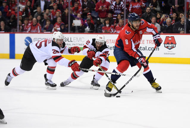 New Jersey Devils defenseman Mirco Mueller (25) and left wing Brian Gibbons (39) try to stop Washington Capitals left wing Alex Ovechkin (8), of Russia, during the third period of an NHL hockey game, Saturday, April 7, 2018, in Washington. The Capitals won 5-3. (AP Photo/Nick Wass)