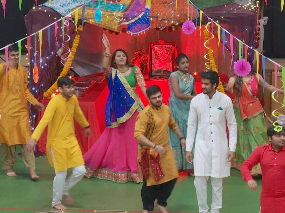 During Navratri, many Hindus participate in Garba, a traditional dance regional to the Indian province of Gujarat that involves large groups of people clad in cultural clothing dancing in circles around a statue of Durga. (Travis Kingdon/CBC - image credit)