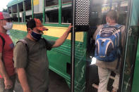 """Expelled migrants board a city bus in Tijuana, Mexico, Oct. 8, 2020. President Donald Trump's reshaping of U.S. immigration policy may be most felt in his undoing of asylum. With immigration laws temporarily suspended at the border during the pandemic, people who enter the U.S. illegally are immediately """"expelled"""" without even a piece of paper to record the incident. (AP Photo/Elliot Spagat)"""