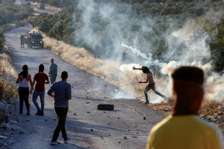 A Palestinian demonstrator returns a tear gas canister during clashes with Israeli soldiers in the town of Tuqua in the Israeli-occupied West Bank on May 28