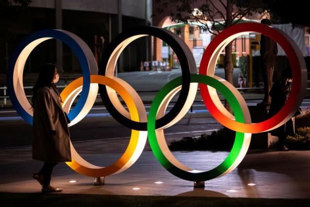 FILE PHOTO: A woman wearing a protective face mask, following the outbreak of the coronavirus, walks past The Olympic rings in front of the Japan Olympics Museum in Tokyo