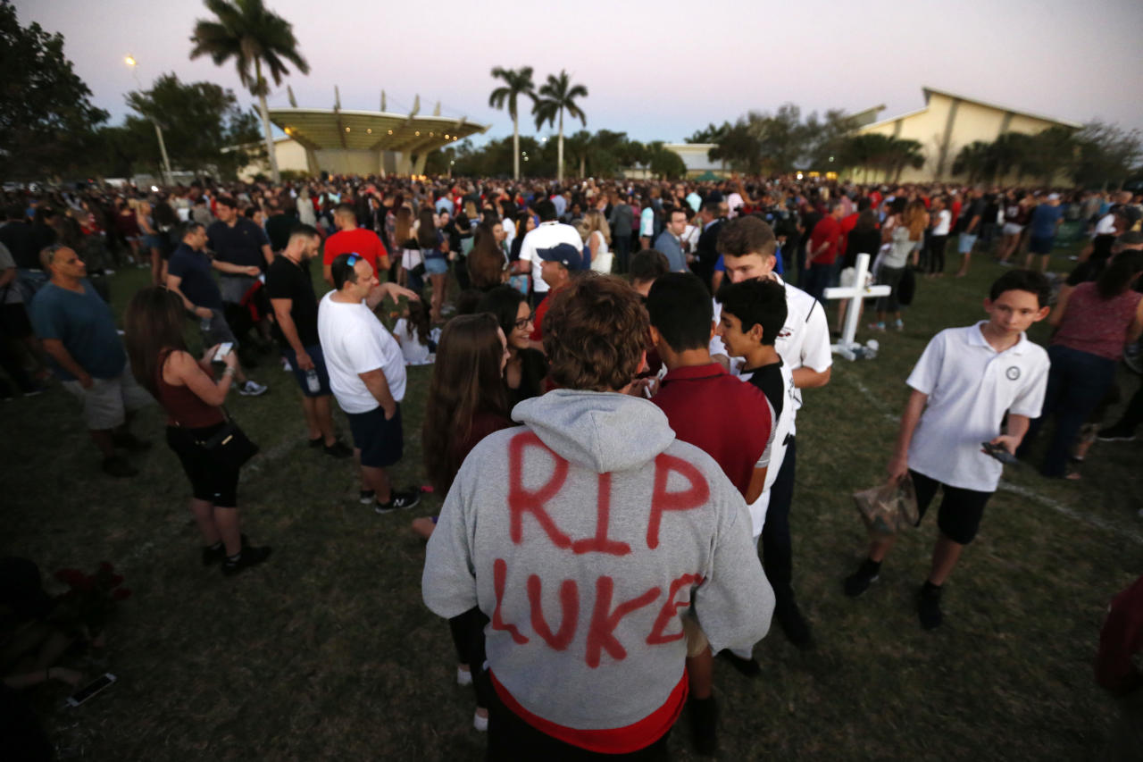 "Zachary Haupert, 14, painted ""RIP Luke,"" on his hoodie in honor of his friend Luke Hoyer, who was one of the victims of the shooting at Marjory Stoneman Douglas High School Wednesday, as he attends a candlelight vigil, Thursday, Feb. 15, 2018, in Parkland, Fla. The teenager accused of using a semi-automatic rifle to kill more than a dozen people and injuring others at a Florida high school confessed to carrying out one of the nation's deadliest school shootings and concealing extra ammunition in his backpack, according to a sheriff's department report released Thursday. (AP Photo/Wilfredo Lee)"