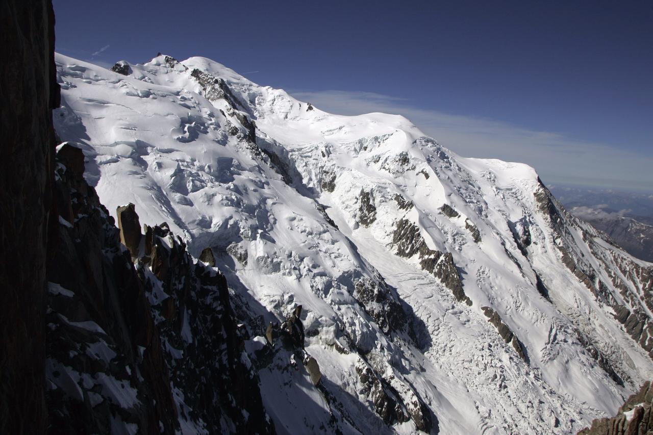 "FILE - In this June 1, 2005 file picture the ""Mont Maudit"", left, and the ""Mont Blanc"" main peak on 4808 meters above sea level are photographed above Chamonix, France. An avalanche in the French Alps on Thursday July 12, 2012 swept six climbers to their deaths, left at least nine injured and about a dozen others unaccounted for, authorities said. Rescuers are searching for the missing. at Mont Maudit, part of the Mont Blanc range. (AP Photo/Keystone/Arno Balzarini)"