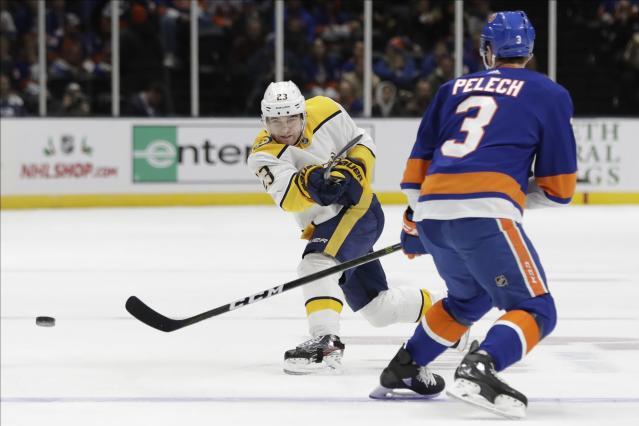 Nashville Predators' Rocco Grimaldi (23) shoots the puck past New York Islanders' Adam Pelech (3) during the first period of an NHL hockey game, Tuesday, Dec. 17, 2019, in Uniondale, N.Y. (AP Photo/Frank Franklin II)