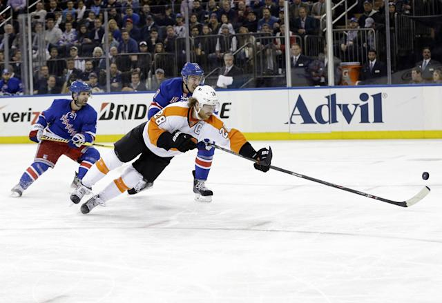 Philadelphia Flyers' Claude Giroux (28) dives past New York Rangers' Martin St. Louis (26) for the puck during the third period in Game 7 of an NHL hockey first-round playoff series onWednesday, April 30, 2014, in New York. The Rangers won the game 2-1. (AP Photo)