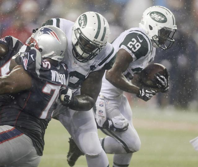 New York Jets running back Bilal Powell (29) runs past New England Patriots defensive tackle Vince Wilfork (75) during the third quarter of an NFL football game Thursday, Sept. 12, 2013, in Foxborough, Mass. (AP Photo/Charles Krupa)