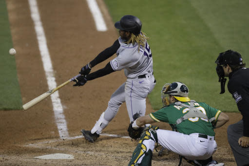 Colorado Rockies' Raimel Tapia swings for an RBI sacrifice fly against the Oakland Athletics in the fifth inning of a baseball game Tuesday, July 28, 2020, in Oakland, Calif. (AP Photo/Ben Margot)