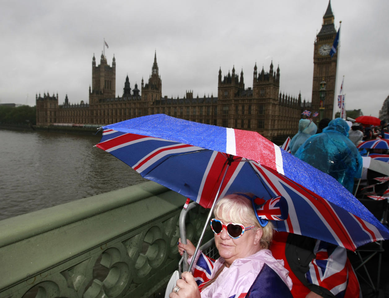 Sue Ridley waits on Westminster Bridge for the Royal Barge to pass the House of Commons and the Big Ben clocktower during the Thames Diamond Jubilee River Pageant in London, Sunday, June 3, 2012. More than 1,000 boats were to sail down the Thames on Sunday in a flotilla tribute to Queen Elizabeth II's 60 years on the throne that organizers are calling the biggest gathering on the river for 350 years. Despite cool, drizzly weather, hundreds of thousands of people are expected to line the riverbanks in London, feting the British monarch whose longevity has given her the status of the nation's favorite grandmother. (AP Photo/Tim Hales)