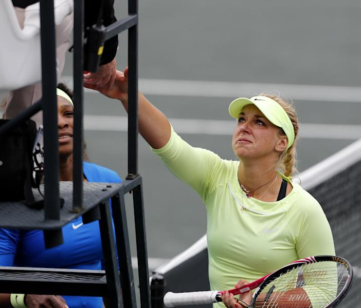 Serena Williams, at left, watches as Sabine Lisicki, of Germany, shakes the chair umpires hand after withdrawing from their quarterfinals match due to a sprained ankle at the Family Circle Cup tennis tournament in Charleston, S.C., Friday, April 6, 2012. (AP Photo/Mic Smith)