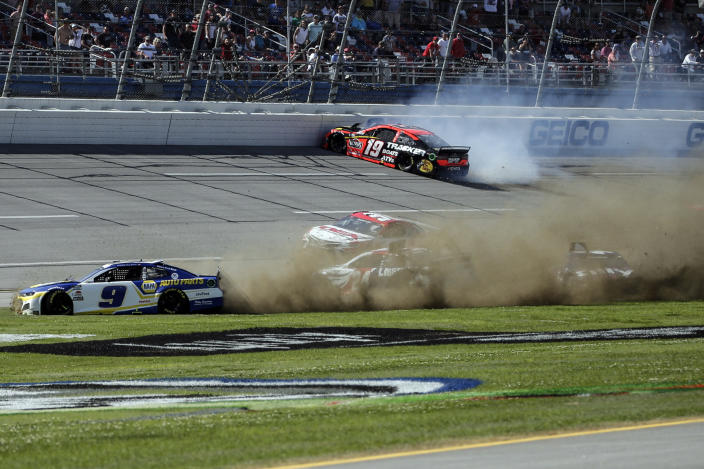NASCAR Cup Series driver Chase Elliott (9), NASCAR Cup Series driver William Byron (24), and NASCAR Cup Series driver Alex Bowman (48) slide through the infield as NASCAR Cup Series driver Martin Truex Jr. (19) hits the outside wall during the Geico 500 NASCAR Sprint Cup auto race at Talladega Superspeedway Sunday, April 25, 2021 in Talladega, Ala. (AP Photo/Butch Dill)