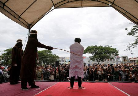 FILE PHOTO: An Indonesian man is publicly caned for having gay sex in Banda Aceh, Aceh province, Indonesia May 23, 2017. Picture taken May 23, 2017. REUTERS/Beawiharta/File Photo