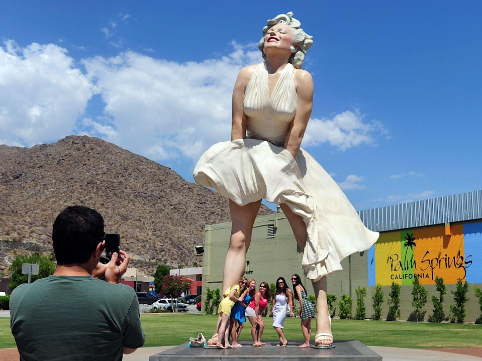 <p>Women pose for a photo beneath the 'Forever Marilyn' statue of actress Marilyn Monroe in Palm Springs, California, on August 4, 2012</p> (AFP via Getty Images)
