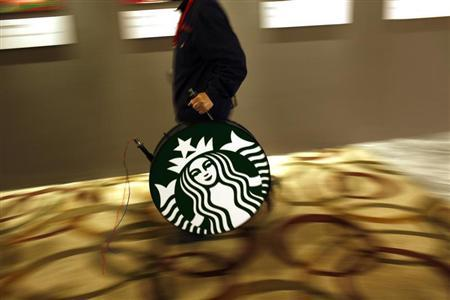A man carries a Starbucks logo sign after a corporate event at a hotel in Shanghai