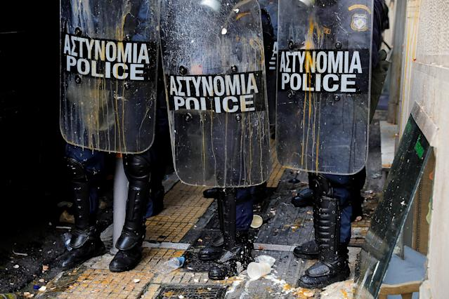 Riot police officers stand guard as leftovers of broken eggs thrown by demonstrators are seen on their shields and on the ground, during a protest outside a notary's office to prevent an e-auction of repossessed properties in Athens, Greece, March 21, 2018. REUTERS/Alkis Konstantinidis TPX IMAGES OF THE DAY