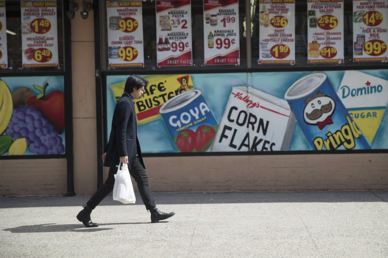 FILE - In this March 27, 2019, file photo a man leaves a supermarket in the East Village neighborhood of Manhattan carrying his groceries in a plastic bag. A growing number of states, counties and cities have passed legislation prohibiting or restricting retailers and other businesses from giving customers single-use plastic bags to carry purchases. Oregon's ban went into effect Jan. 1, 2020 and Maine, New York state and Vermont have similar prohibitions going into effect later in the year. (AP Photo/Mary Altaffer, Fil)