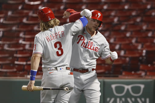 Philadelphia Phillies' Rhys Hoskins is congratulated by teammate Bryce Harper (3) after hitting a solo home run against the Boston Red Sox during the fifth inning of a baseball game Tuesday, Aug. 18, 2020, at Fenway Park in Boston. (AP Photo/Winslow Townson)