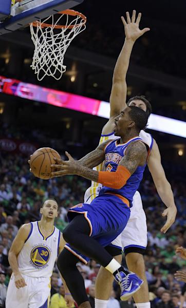 New York Knicks' J.R. Smith lays up a shot against Golden State Warriors' Andrew Bogut during the first half of an NBA basketball game Monday, March 11, 2013, in Oakland, Calif. (AP Photo/Ben Margot)
