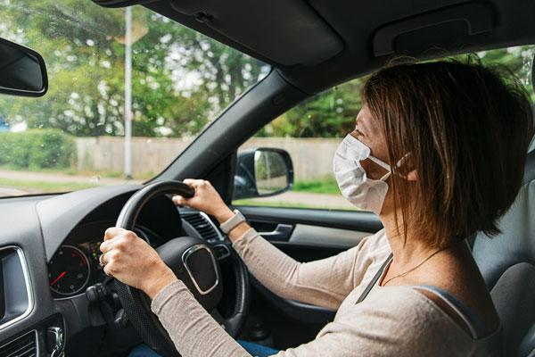 Woman with mask driving car